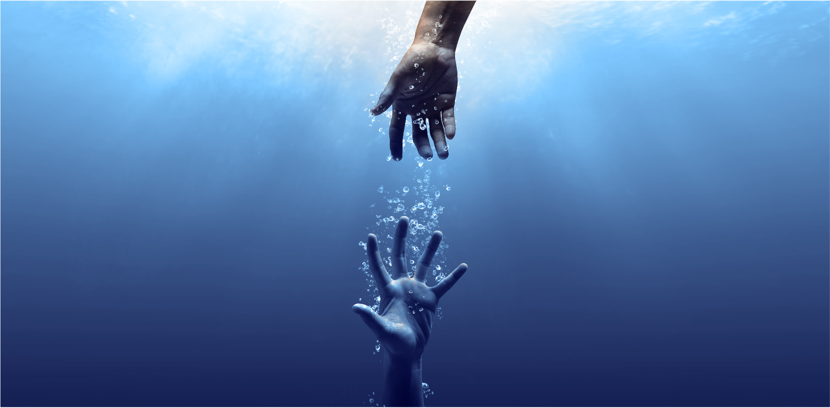 two hands reaching for each other underwater