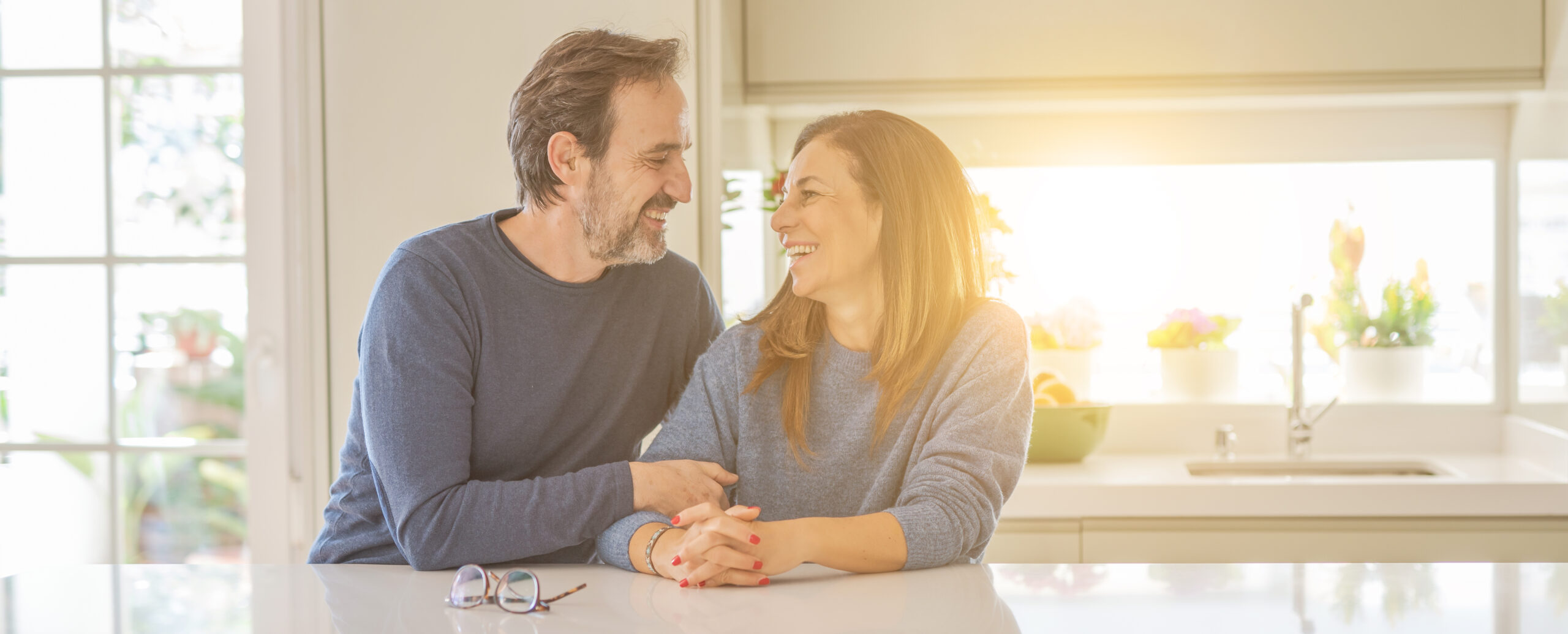 Middle age couple sitting together at home laughing and staring at each other in their kitchen.