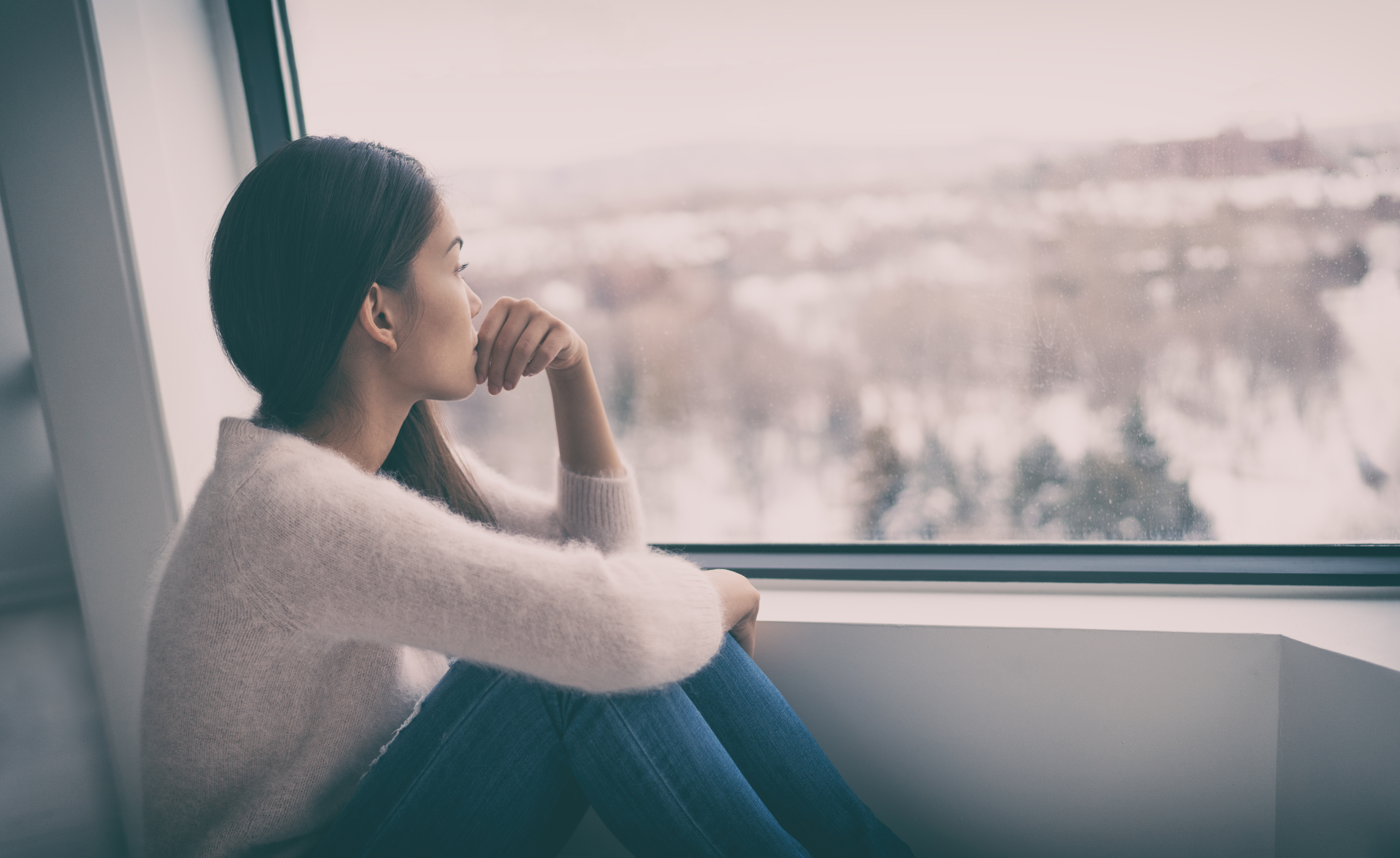 a women who looks sad is staring out of a window