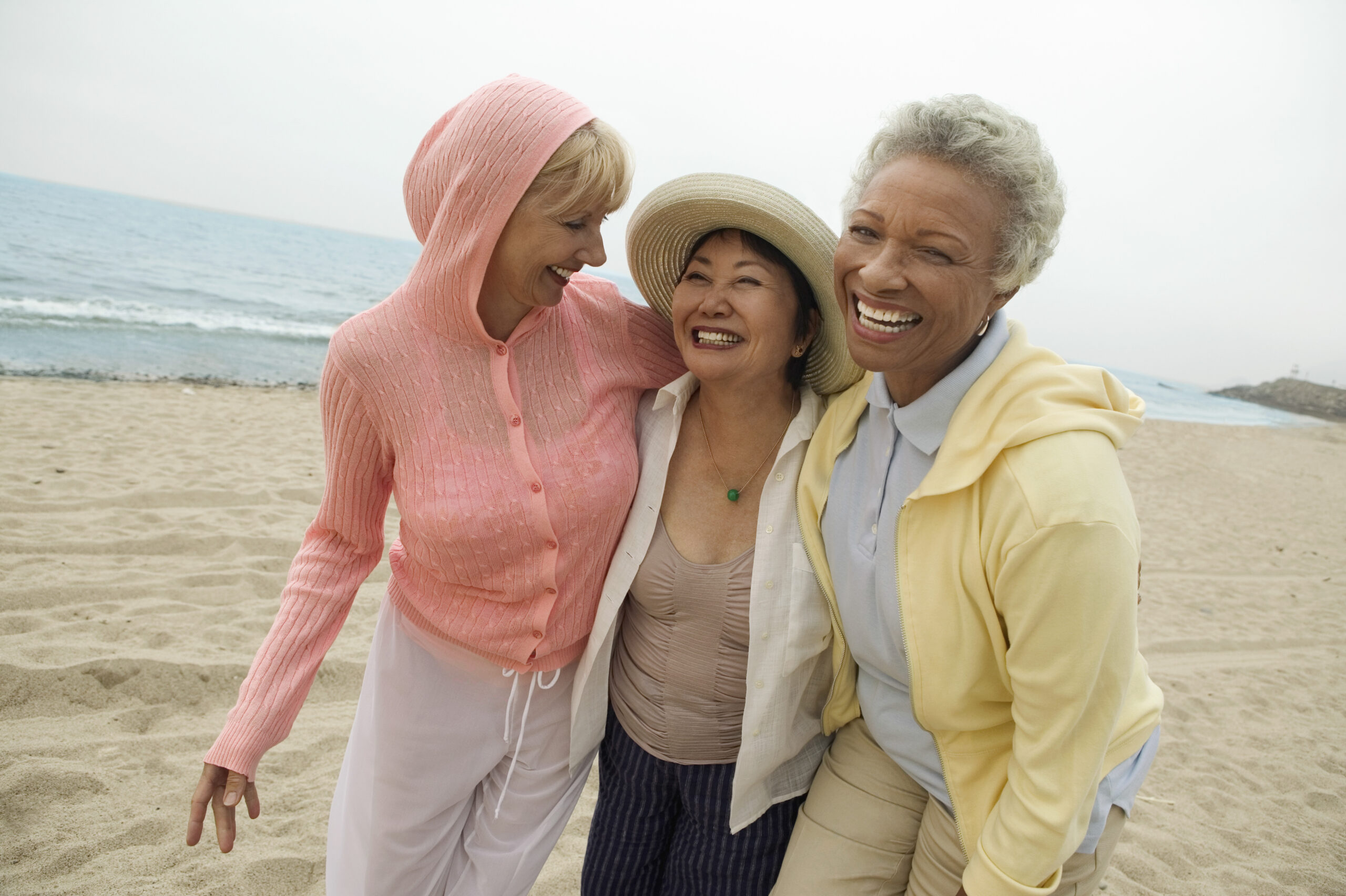 happy middle aged female friends enjoying vacation at beach, They are all laughing and smiling