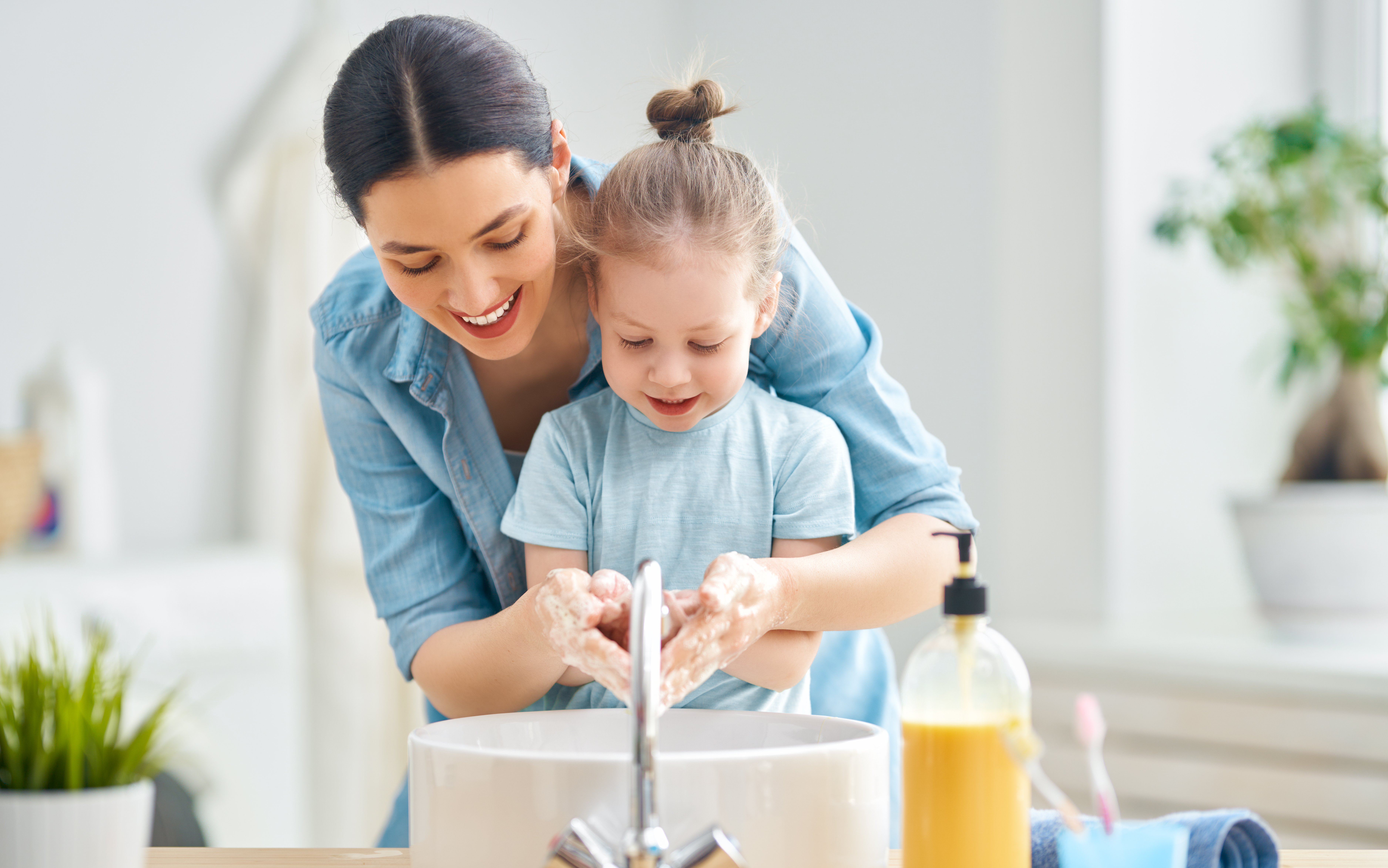 A mom with her daughter washing their hands over a sink in the kitchen