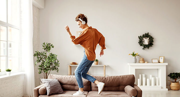Cheerful woman listening to music and dancing on couch at home in living room