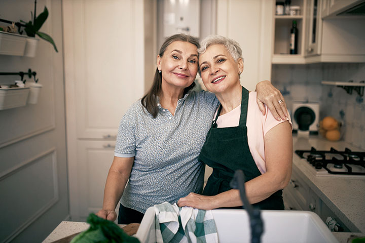 Two elderly females posing in kitchen. They are smiling and preparing a healthy meal together,