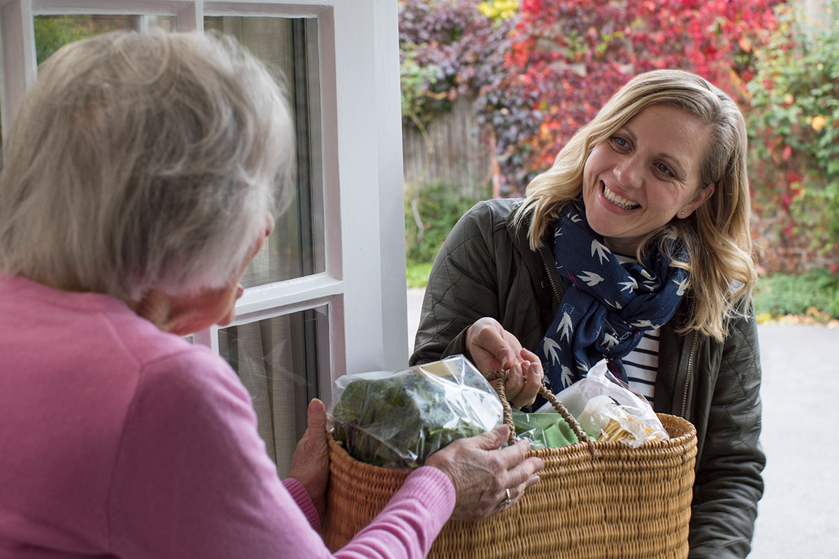 Female Neighbor Helping Senior Woman by bringing her food and groceries to her door