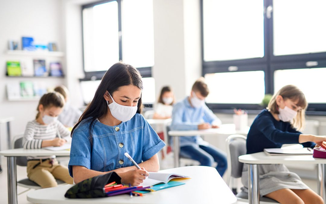 Masked children in a classroom at their individual desks. They are doing school work