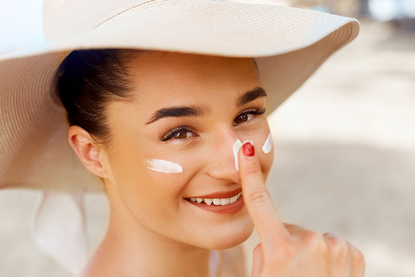 Young woman with a beach hat on is smiling and applying sunscreen on her face.