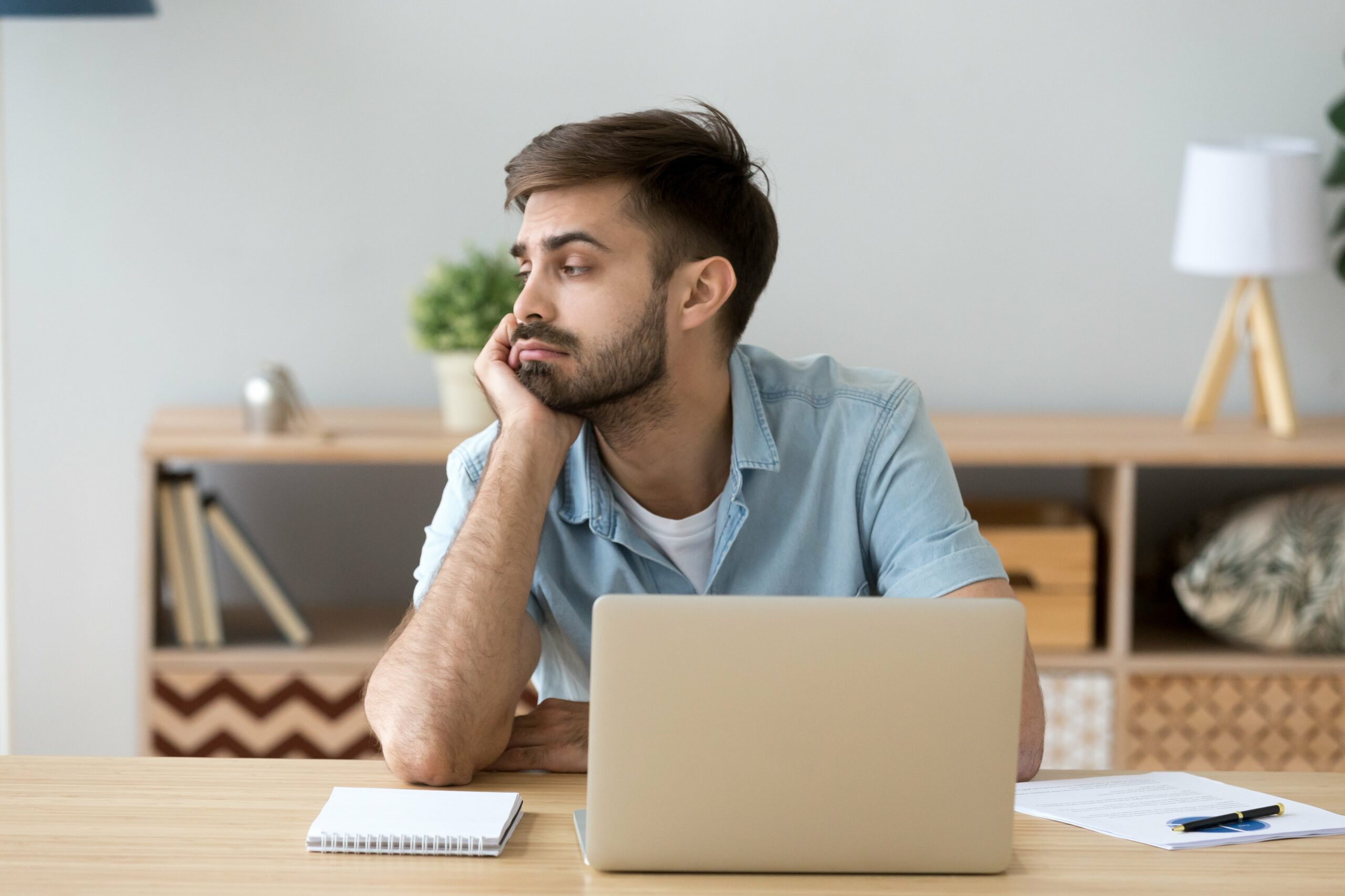 A man sitting at a desk with his laptop open, looking sad and without focus.