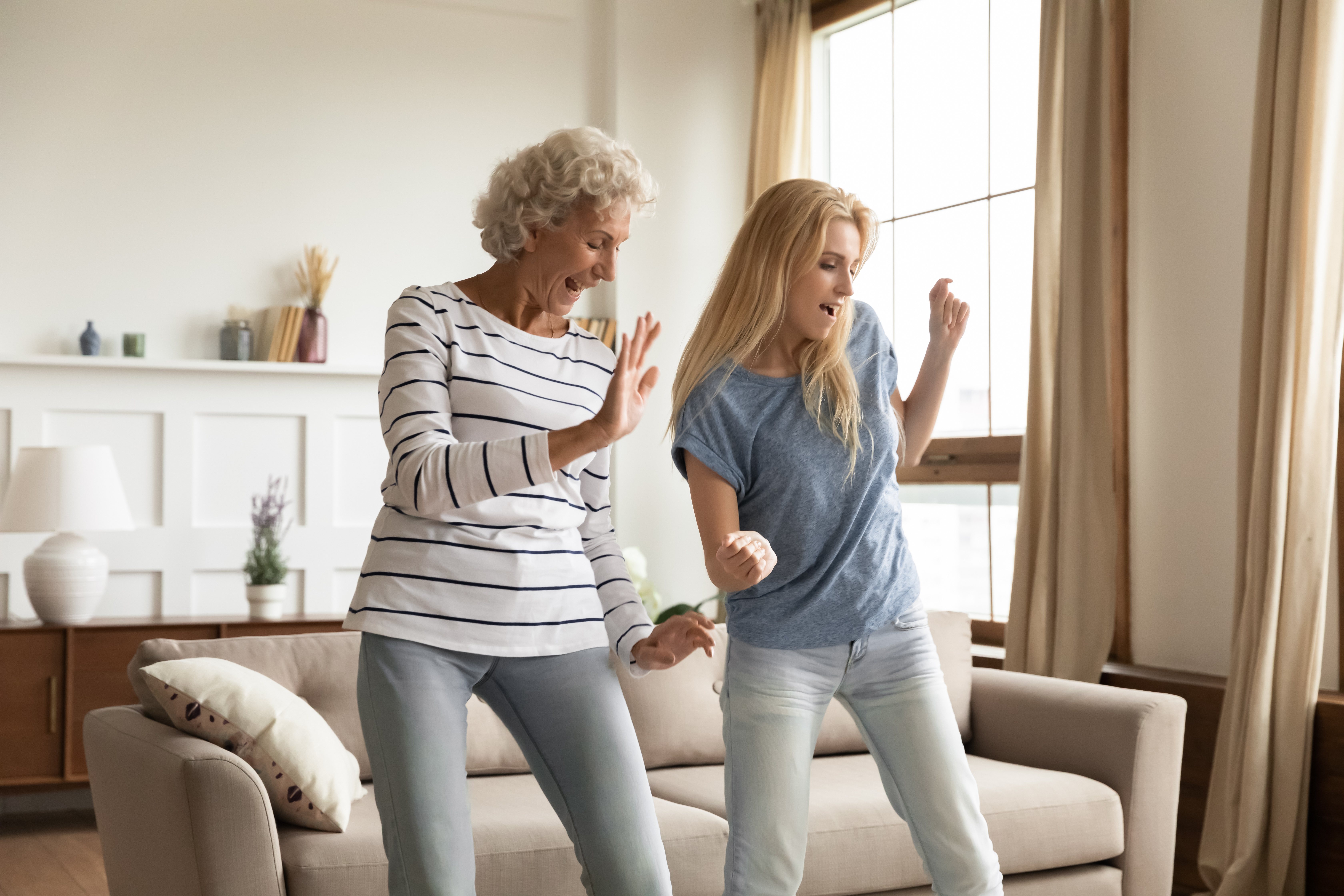 Older woman and a younger woman, happily dancing together in a living room